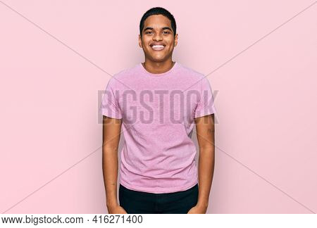 Young handsome hispanic man wearing casual pink t shirt looking positive and happy standing and smiling with a confident smile showing teeth