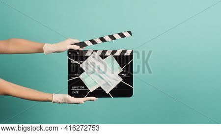 Hand Wear Medical Gloves And Hold Black Clapperboard Or Movie Slate With Face Mask. It Use In Movies