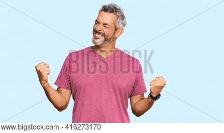 Middle age grey-haired man wearing casual clothes very happy and excited doing winner gesture with arms raised, smiling and screaming for success. celebration concept.