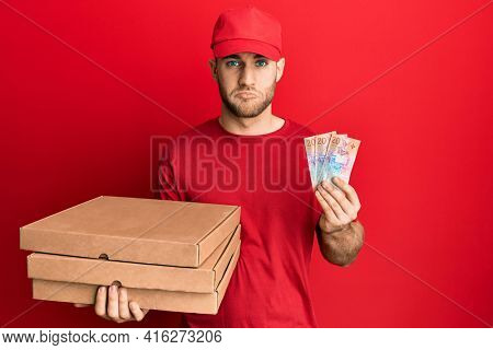 Young caucasian man holding delivery box and swiss franc banknotes depressed and worry for distress, crying angry and afraid. sad expression.