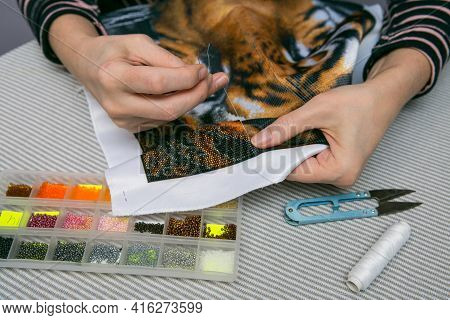 Bead Embroidery Process. Close-up - Female Hands String Beads On A Needle And Sew Them To The Fabric