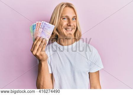 Caucasian young man with long hair holding thai baht banknotes looking positive and happy standing and smiling with a confident smile showing teeth