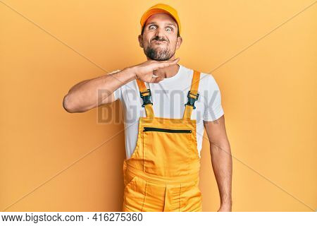Young handsome man wearing handyman uniform over yellow background cutting throat with hand as knife, threaten aggression with furious violence