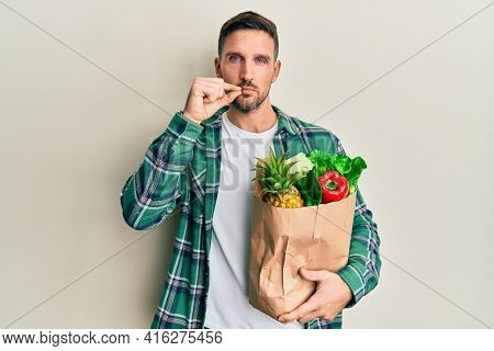 Handsome man with beard holding paper bag with groceries mouth and lips shut as zip with fingers. secret and silent, taboo talking