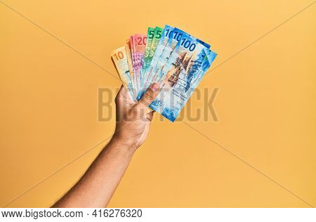 Hand of hispanic man holding swiss franc banknotes over isolated yellow background.