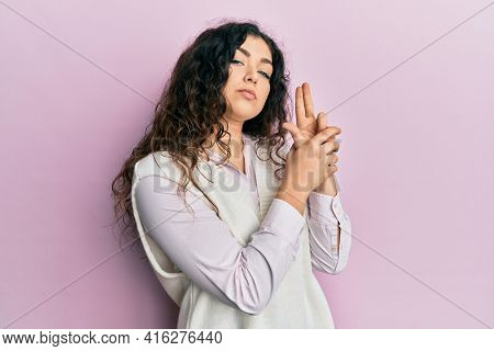 Young brunette woman with curly hair wearing casual clothes holding symbolic gun with hand gesture, playing killing shooting weapons, angry face