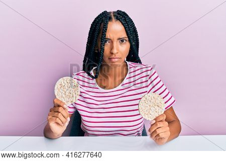 Beautiful hispanic woman eating healthy rice crackers skeptic and nervous, frowning upset because of problem. negative person.