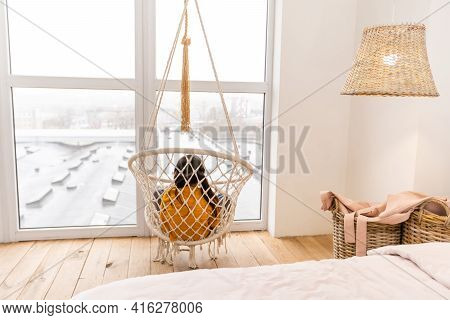 A Beautiful Young Dark-haired Girl Relaxes In A Swing. Cute Brunette Girl Swinging In A Woven Chair