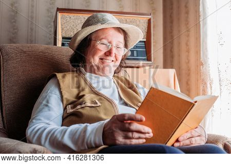 Elderly Woman With A Hat On, Reading A Book By The Window. Smiling, Felling Happy. Afternoon Light