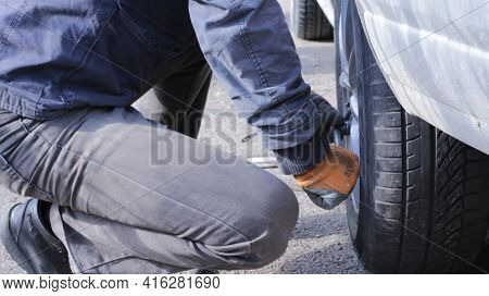 A Man With Effort Fixes Or Spins A Wheel On A Car By Hand, Squatting On The Asphalt, The Process Of