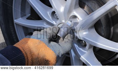 A Hand In A Glove Brings A Bolt To The Hole Of A Car Wheel, A Service Worker Takes Out A Bolt For Fa