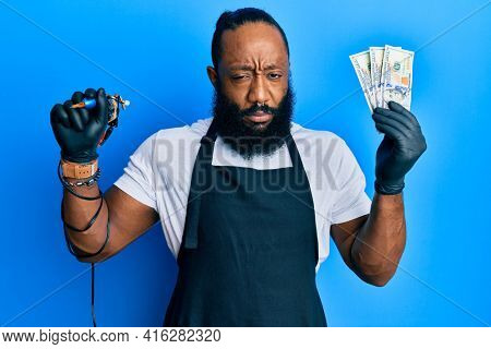 Young african american man tattoo artist wearing professional uniform and gloves holding tattooer machine and usa dollars banknotes skeptic and nervous, frowning upset because of problem. negative