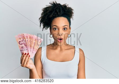 Young african american girl holding thai baht banknotes scared and amazed with open mouth for surprise, disbelief face