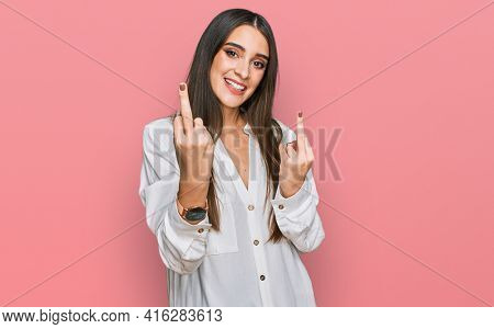 Young beautiful woman wearing casual white shirt showing middle finger doing fuck you bad expression, provocation and rude attitude. screaming excited