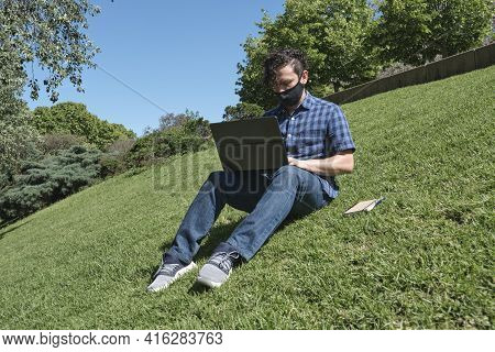 Young Man Wearing A Cloth Face Mask Working Or Studying Using A Laptop Sitting In A Park. Concepts O