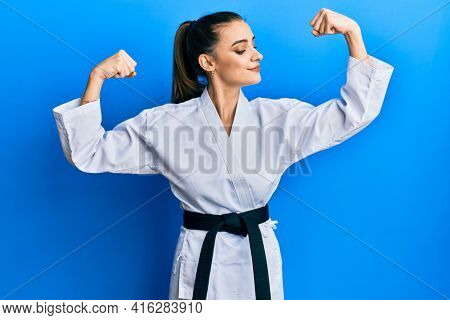 Beautiful brunette young woman wearing karate fighter uniform with black belt showing arms muscles smiling proud. fitness concept.