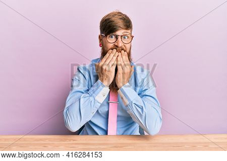 Young irish redhead man wearing business shirt and tie sitting on the table laughing and embarrassed giggle covering mouth with hands, gossip and scandal concept