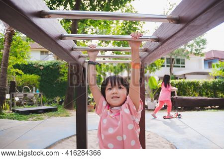Asian Girls Are Playing On Playground With Trapeze. Active Child Hangs On Bar With Two Hands. Childr