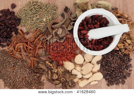 Traditional chinese herbal medicine selection with mortar and pestle over papyrus background.