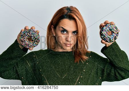 Hispanic young woman holding tasty colorful doughnuts skeptic and nervous, frowning upset because of problem. negative person.
