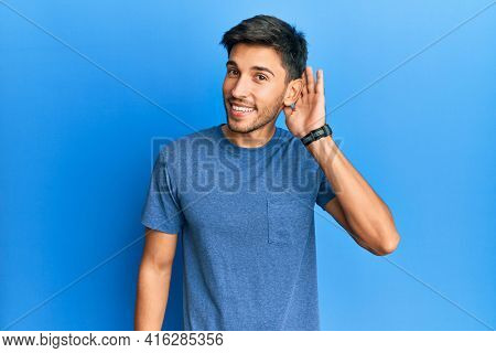Young handsome man wearing casual tshirt over blue background smiling with hand over ear listening and hearing to rumor or gossip. deafness concept.
