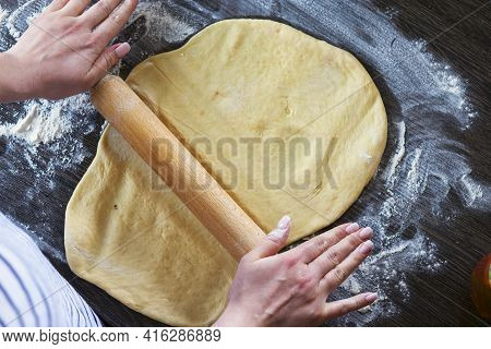 Hands, Rolling-pin And Dough For Bread, Pasta Or Pizza On Wooden Table. The Process Of Making Dough