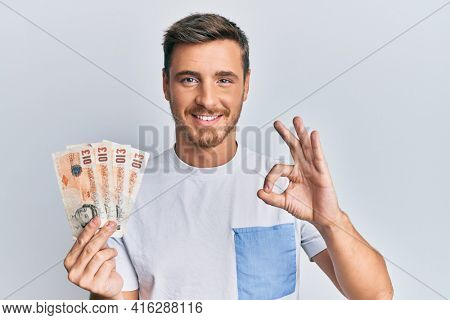 Handsome caucasian man holding 10 united kingdom pounds banknotes doing ok sign with fingers, smiling friendly gesturing excellent symbol