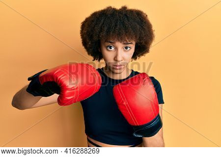 Young hispanic sporty girl using boxing gloves skeptic and nervous, frowning upset because of problem. negative person.