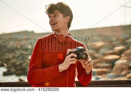Young hispanic man smiling happy using reflex camera at the beach
