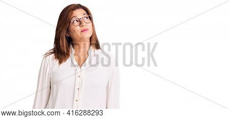 Middle age latin woman wearing casual clothes and glasses smiling looking to the side and staring away thinking.