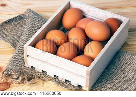 Raw brown eggs in wooden box on canvas fabric on wooden table.