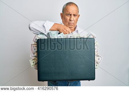 Handsome senior man holding briefcase full of dollars skeptic and nervous, frowning upset because of problem. negative person.