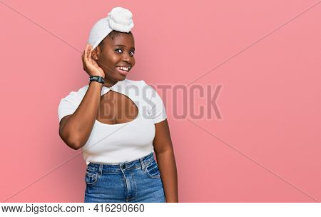 Young african woman with turban wearing hair turban over isolated background smiling with hand over ear listening an hearing to rumor or gossip. deafness concept.
