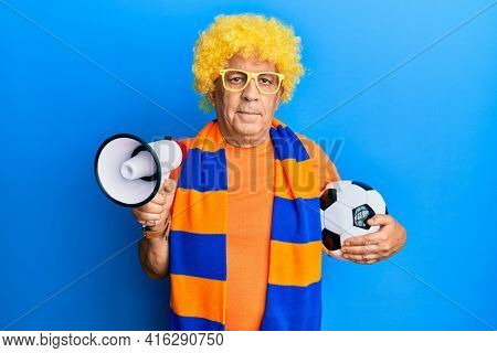 Senior hispanic man football hooligan cheering game holding ball and megaphone relaxed with serious expression on face. simple and natural looking at the camera.