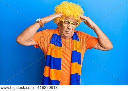 Senior hispanic man football hooligan cheering game with hand on head, headache because stress. suffering migraine.