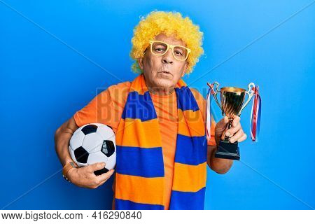 Senior hispanic man football hooligan cheering game holding ball and trophy looking at the camera blowing a kiss being lovely and sexy. love expression.