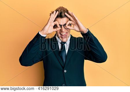 Handsome caucasian man wearing business suit and tie doing ok gesture like binoculars sticking tongue out, eyes looking through fingers. crazy expression.