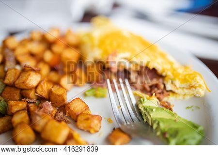 Half-eaten Omelette And Roasted Potatoes On A White Plate