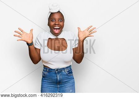 Young african woman with turban wearing hair turban over isolated background celebrating crazy and amazed for success with arms raised and open eyes screaming excited. winner concept