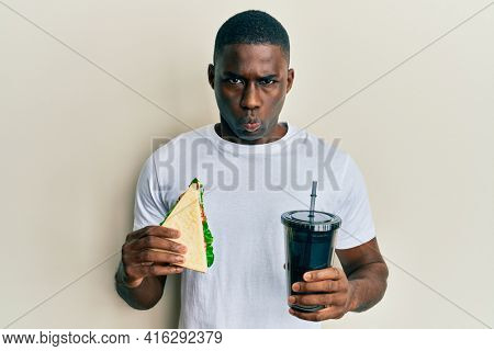 Young african american man eating sandwich and drinking soda skeptic and nervous, frowning upset because of problem. negative person.