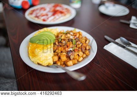 Omelette, Roasted Potatoes And Avocado Slices On A White Plate