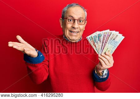 Handsome senior man with grey hair holding egyptian pounds banknotes celebrating achievement with happy smile and winner expression with raised hand