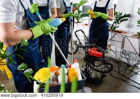 Cropped View Of Cleaner In Rubber Gloves Holding Detergent Near Colleagues And Vacuum Cleaner In Off