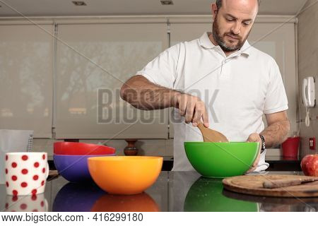 Caucasian Man, Between 30-39 Years Old, Stirring The Mixture In A Bowl, With A Wooden Spoon, To Prep