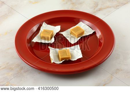 Three Creamy Caramel Candy Squares In Open Candy Wrappers On Red Snack Plate
