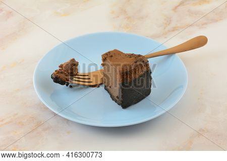 Slice Of Belgian Chocolate Cheesecake With Missing Bite And Copper Fork On Blue Dessert Plate