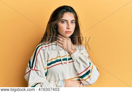 Young caucasian woman wearing casual clothes touching painful neck, sore throat for flu, clod and infection