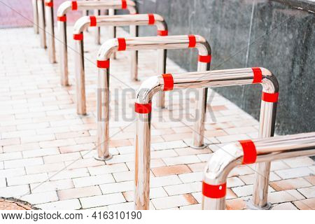 Tubular Structure Stainless Steel Bicycle Parking With Red Stripes Installed On The Street Sidewalk.