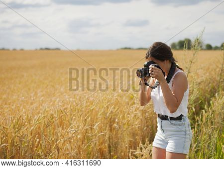 Girl Photographer With A Camera In A Wheat Field. Woman Photographer Stands In A Field With A Camera