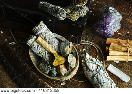 A Close Up Image Of White Sage Smudge Sticks With Rough Crystals And Selenite On A Dark Wooden Table